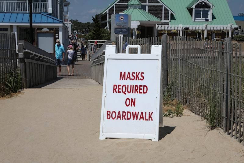 A sign sits on the entryway to a crowded Bethany Beach on a warm breezy Wednesday, June 10. Masks are required on the boardwalk but not the beach.