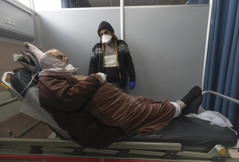 Ibrahim Abu Safiya attends to his mother who is infected with COVID-19 while she is under medical observation at the emergency unit, of the Palestine Medical Complex, in the West Bank city of Ramallah, Tuesday, March 2, 2021. (AP Photo/Nasser Nasser)