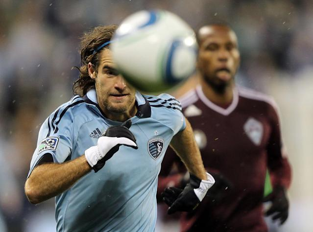 KANSAS CITY, KS - NOVEMBER 02: Graham Zusi #8 of Sporting Kansas City chases a ball as Miguel Comminges #32 of the Colorado Rapids looks on during the MLS playoff game on November 2, 2011 at LiveStrong Sporting Park in Kansas City, Kansas. (Photo by Jamie Squire/Getty Images)