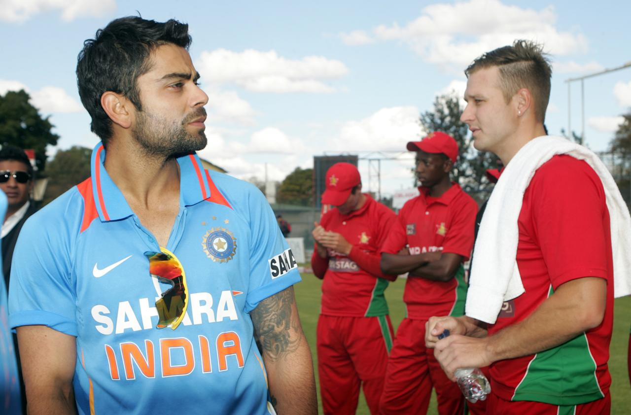 India captain Virat Kohli (l)  stands with Zimbabwe bowler Kyle Jarvis  after winning the final game of the 5 match cricket ODI series between hosts Zimbabwe and India at Queens Sports Club in Harare on August 3, 2013. AFP PHOTO /Jekesai Njikizana.        (Photo credit should read JEKESAI NJIKIZANA/AFP/Getty Images)