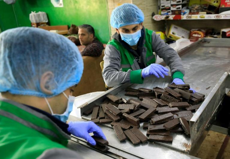 Workers at al-Arees sweets factory in Gaza City sort a batch of chocolate-covered biscuits