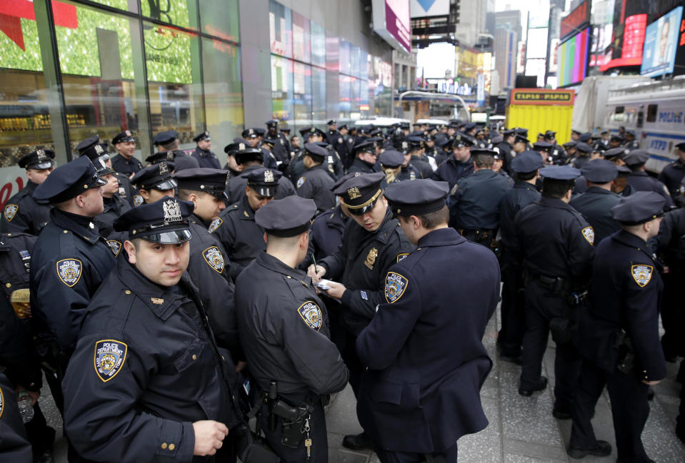 FILE - In this Dec. 31, 2015, file photo, police officers gather at the southern end of Times Square to receive their assignments for New Year's Eve in New York. Although New York City police have turned to familiar tactics ahead of the iconic Thursday, Dec. 31, 2020, ball drop, the department's playbook this year includes an unusual mandate: preventing crowds from gathering in Times Square. (AP Photo/Seth Wenig, File)
