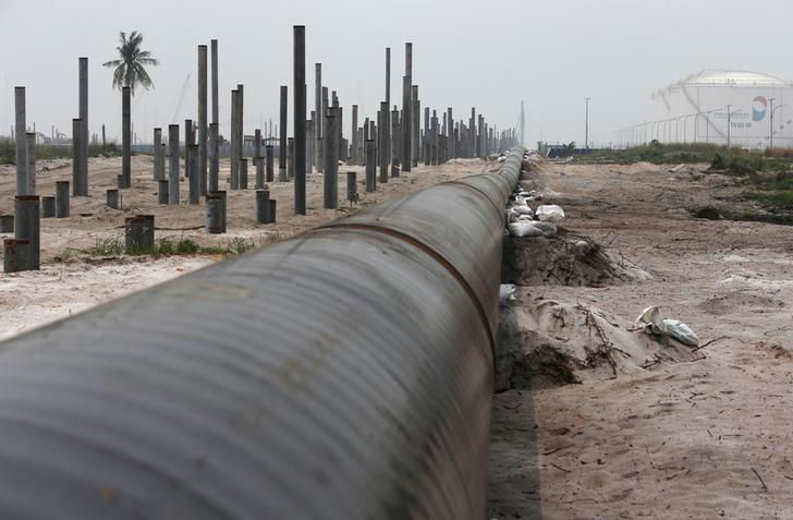 An oil pipeline is laid next to the Vopak-Dialog oil storage facility (R) and a Refinery and Petrochemical Integrated Development (RAPID) project construction site in Pangerang in Malaysia's southern state of Johor October 6, 2015. REUTERS/Edgar Su