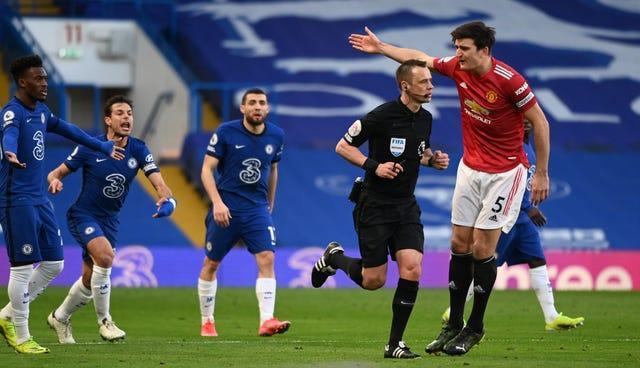 Chelsea players make their feelings known towards Manchester United's Harry Maguire after Stuart Attwell does not award a penalty after a VAR check