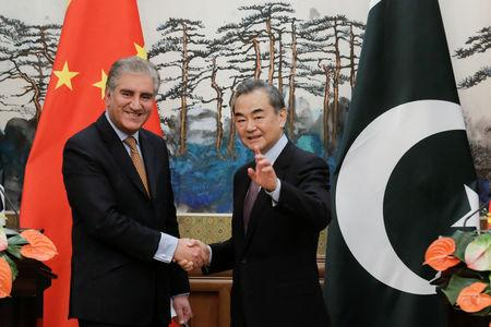 Chinese Foreign Minister Wang Yi and Pakistani Foreign Minister Shah Mehmood Qureshi shake hands after a news conference at the Diaoyutai State Guesthouse in Beijing, China March 19, 2019. REUTERS/Thomas Peter