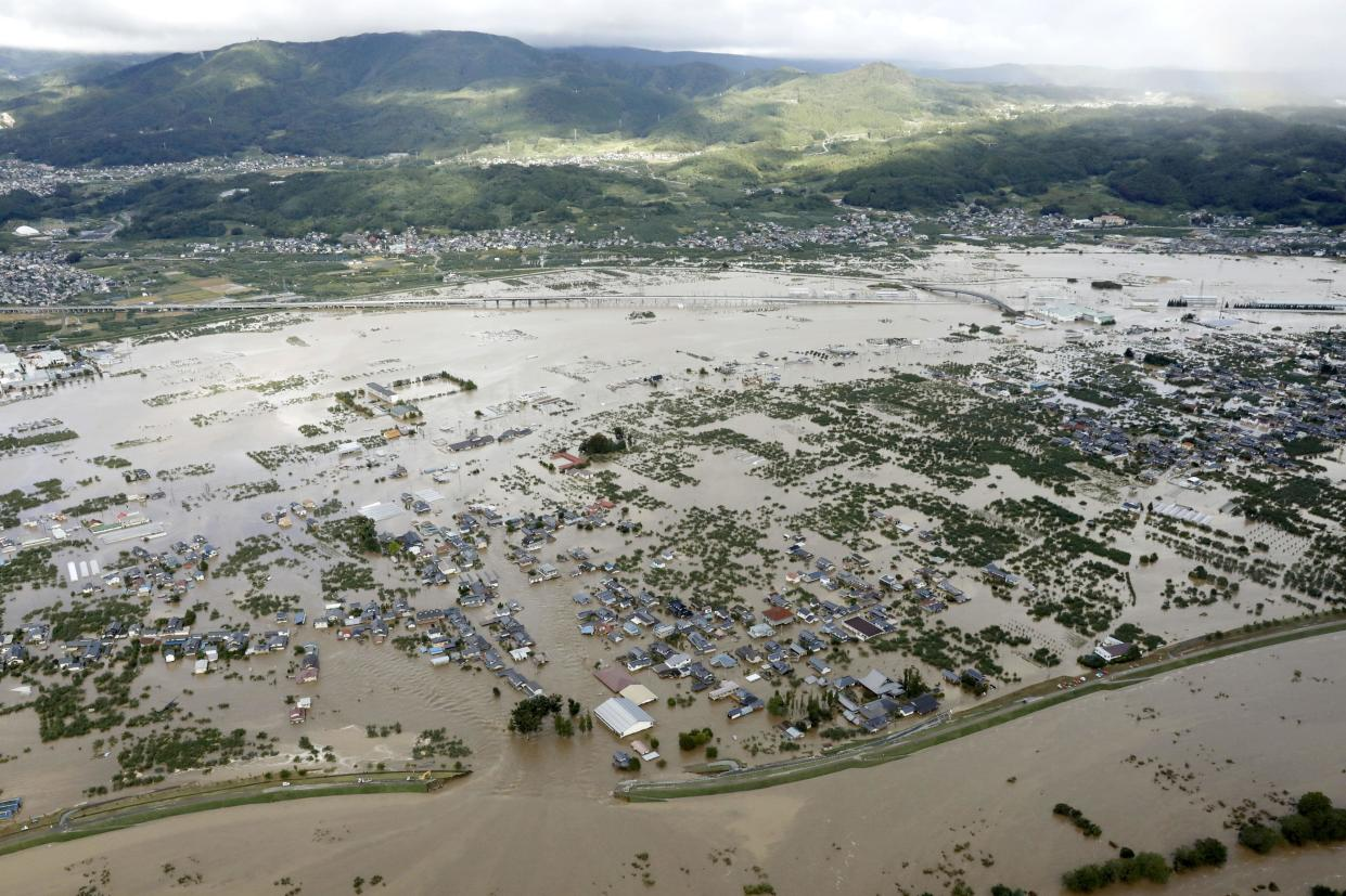 A residential area is submerged in muddy waters after an embankment of the Chikuma River, bottom, broke because of Typhoon Hagibis, in Nagano, central Japan, Oct. 13, 2019. (Photo: Yohei Kanasashi/Kyodo News via AP)