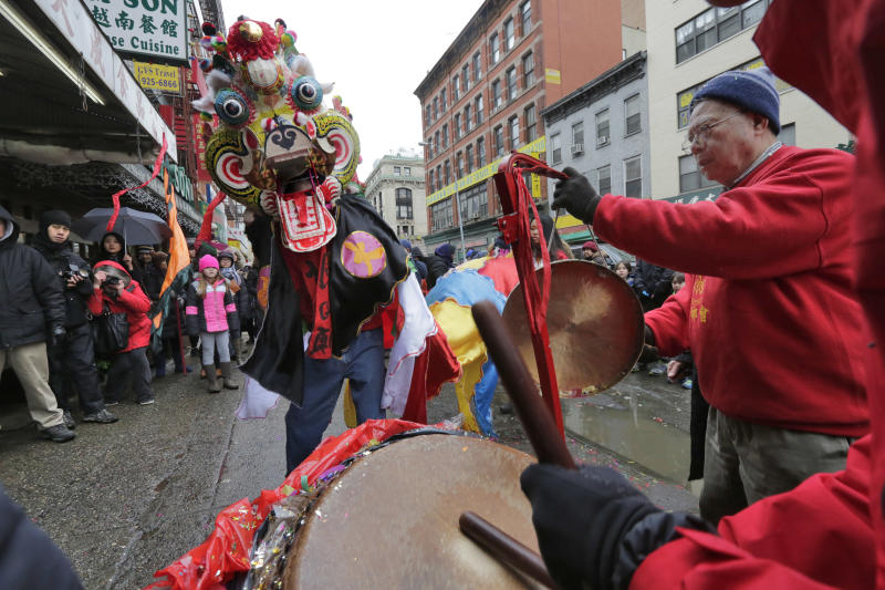 FILE - In this Feb. 8, 2016, file photo, a lion dancer is accompanied by a drummer and gong during a Lunar New Year celebration in New York's Chinatown neighborhood. The 2017 Lunar New Year holiday, celebrating the year of the rooster, begins Jan. 28. New York is one of a number of cities around the country that hosts parades with lion dancers. This year's procession in Manhattan's Chinatown is scheduled to take place Feb. 5. (AP Photo/Richard Drew, File)