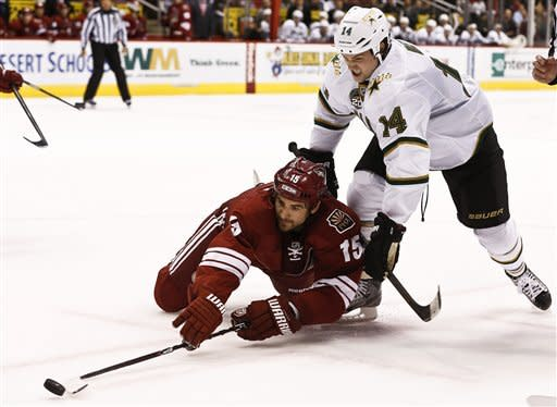 Phoenix Coyotes' Boyd Gordon (15) tries to get control of the puck as he is shoved by Dallas Stars' Jamie Benn (14) during the first period in an NHL hockey game Saturday, Feb. 2, 2013, in Glendale, Ariz. (AP Photo/Ross D. Franklin)