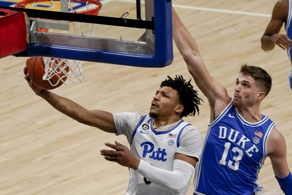 Pittsburgh's Ithiel Horton, left, shoots after getting by Duke's Joey Baker (13) during the first half of an NCAA college basketball game, Tuesday, Jan. 19, 2021, in Pittsburgh. (AP Photo/Keith Srakocic)