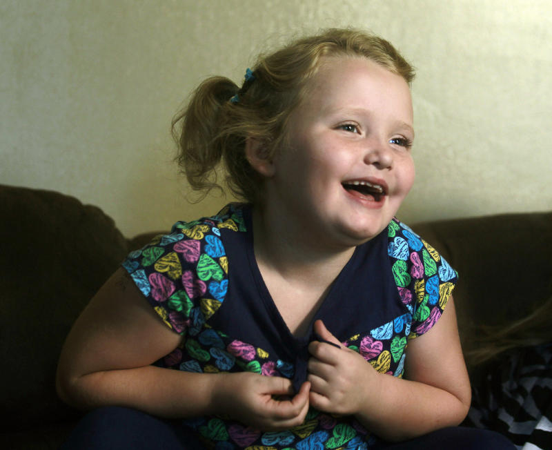 """FILE - In this Sept. 10, 2012 file photo, seven-year-old beauty pageant regular and reality show star Alana """"Honey Boo Boo"""" Thompson gestures during an interview in her home in McIntyre, Ga. The TLC network said Wednesday that it has ordered Halloween, Thanksgiving and Christmas specials focusing on its seven-year-old breakout star Honey Boo Boo. The series airs its 10th and final episode of its debut season on Wednesday, Sept. 26. (AP Photo/John Bazemore)"""