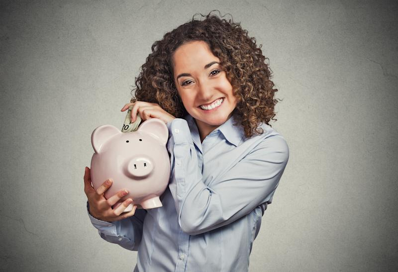 Smiling woman putting money in piggy bank.