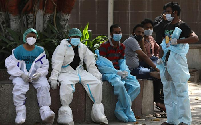 Health workers rest in between cremating Covid-19 victims in New Delhi, India - Manish Swarup/AP
