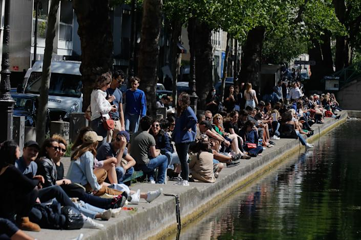 People sit on a bank of the Canal Saint-Martin in Paris, on May 16, 2020, on the first weekend after France eased lockdown measures. (Photo: FRANCOIS GUILLOT via Getty Images)