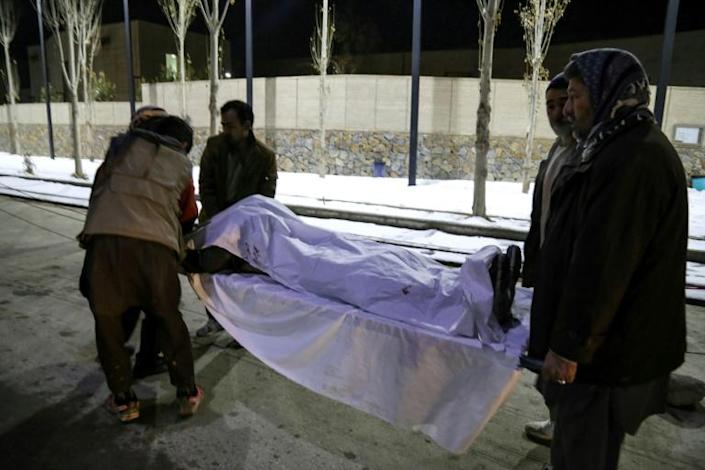 Volunteers carry the body of a victim to a hospital following attacks in Bamiyan on November 24, 2020