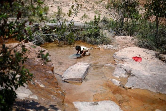 An Indigenous child works at a gold mine in the Santa Creuza community in the Raposa Serra do Sol reservation