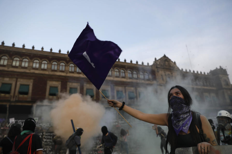 A woman waves a feminist flag as demonstrators attempt to storm the National Palace during a march to commemorate International Women's Day and protesting against gender violence, in Mexico City, Monday, March 8, 2021. (AP Photo/Rebecca Blackwell)