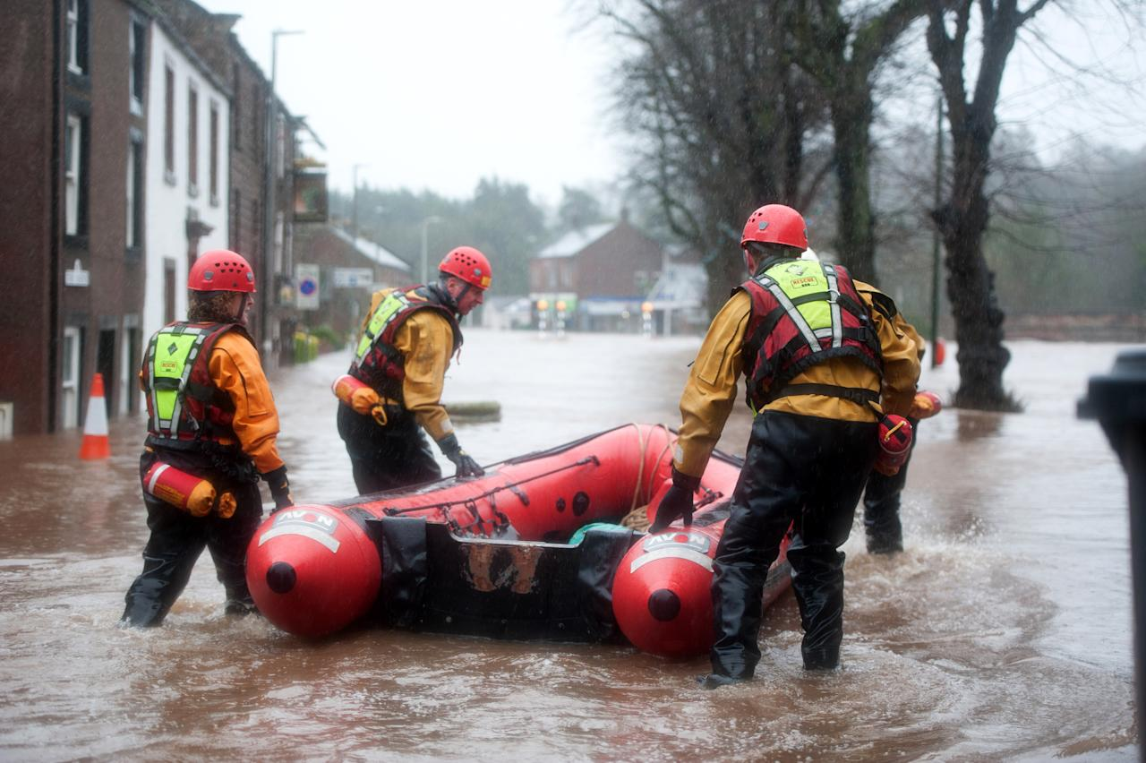 Dozens evacuated from homes after heavy rain causes floods and travel chaos in north-west and Wales