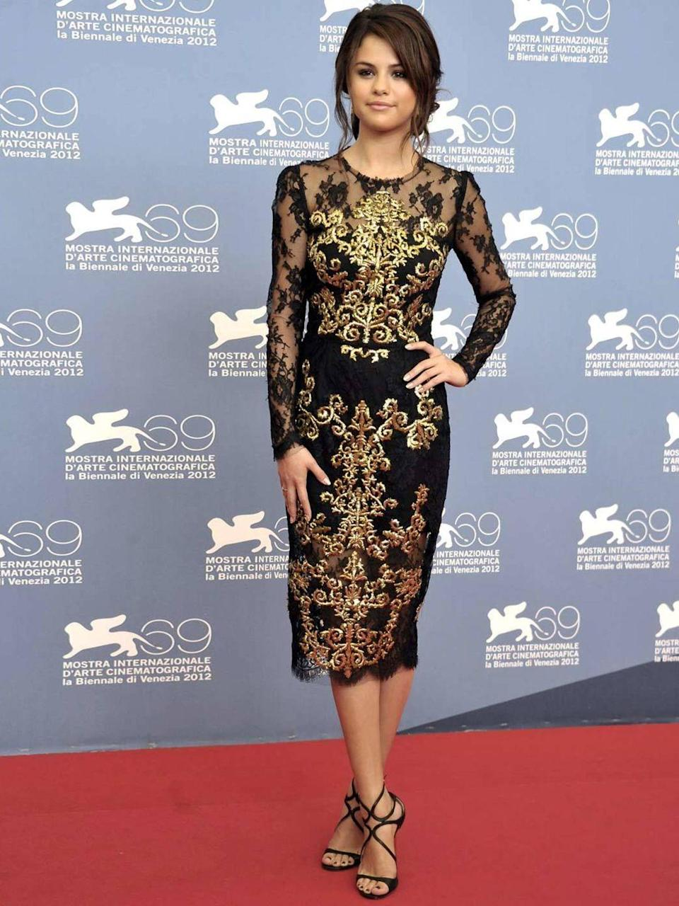 <p>Selena Gomez arrives for the Spring Breakers photocall wearing an ornate gold and black dress by Dolce & Gabbana, September 2012.</p>