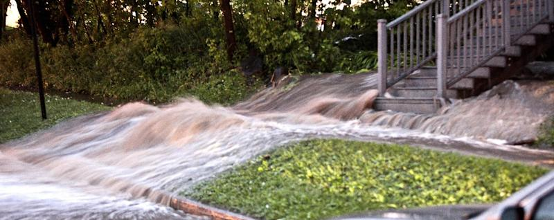 Floodwaters rush past a home in Duluth, Minn., Tuesday, June 19, 2012, after heavy rains hit the area. Floods fed by a steady torrential downpour forced road closures in northeastern Minnesota on Wednesday, and some people were being urged to evacuate their homes because of the rising St. Louis River. Interstate 35 and downtown tunnels in Duluth were closed and police recommended emergency travel only, warning that numerous sinkholes and washouts were making travel dangerous. (AP Photo/The Duluth News-Tribune, Clint Austin)
