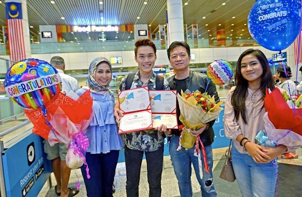 Muhamad Shahmeer Mohd Nashrul (second left) won second place in the Mandarin language competition at the 16th Chinese Bridge Chinese Proficiency Competition for Foreign College Students, in Changsha, is pictured on his arrival at KLIA, August 16, 2017. — Bernama pic