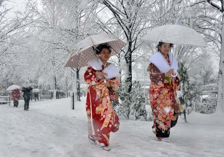 Women dressed in kimonos walk on a snow covered street to a coming-of-age ceremony in Tokyo on January 14, 2013