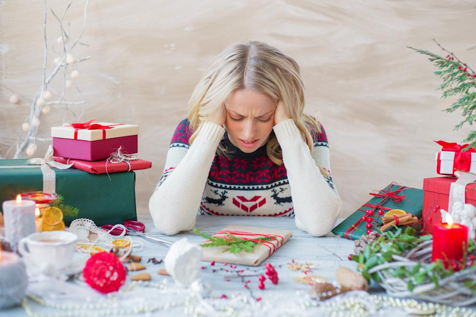 Exhausted and overwhelmed woman packing Christmas gifts