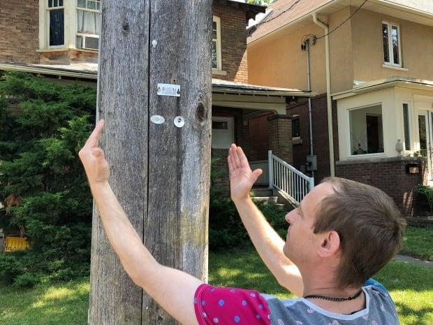 Chad Barnard shows where the CCTV camera was installed on his street. Before it was removed, the camera pointed directly into his bedroom window, he said. (Rob Krbavac/CBC - image credit)