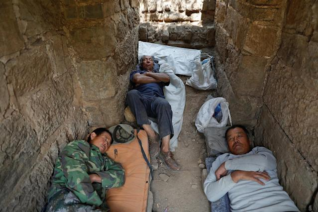 <p>People rest after working on the reconstruction of the Jiankou section of the Great Wall, located in Huairou District, north of Beijing, China, June 7, 2017. (Photo: Damir Sagolj/Reuters) </p>