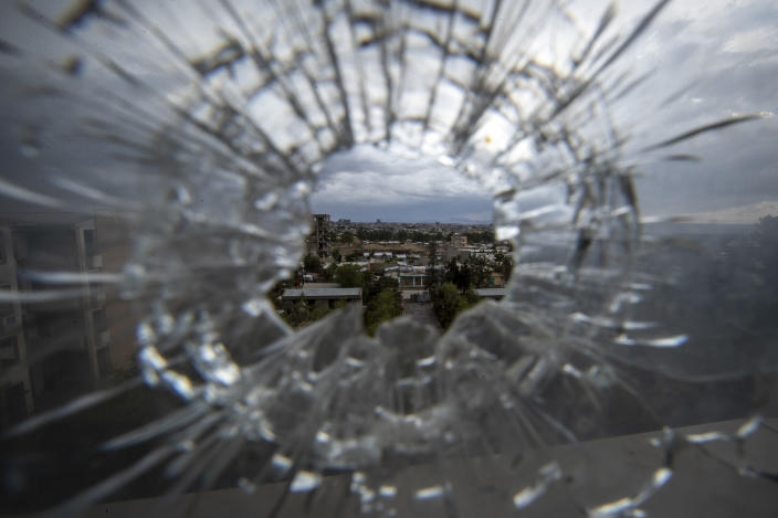 """FILE - In this Thursday, May 6, 2021 file photo, the city of Mekele is seen through a bullet hole in a stairway window of the Ayder Referral Hospital, in the Tigray region of northern Ethiopia. Ethiopia's government said in a statement carried by state media Monday, June 28, 2021, that it has """"positively accepted"""" a call for an immediate, unilateral cease-fire in its Tigray region after nearly eight months of deadly conflict. (AP Photo/Ben Curtis, File)"""