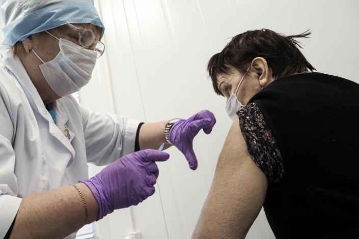 A Russian medical worker administers a shot of Russia's Sputnik V coronavirus vaccine to 75-year-old Maria Piparinen in a local rural medical post in the village of Ikhala in Russia's Karelia region, Tuesday, Feb. 16, 2021. Piparinen and other elderly residents were relieved when they heard that doctors were finally bringing a few doses of the coronavirus vaccine to their remote, snowy village. (AP Photo/Dmitri Lovetsky)