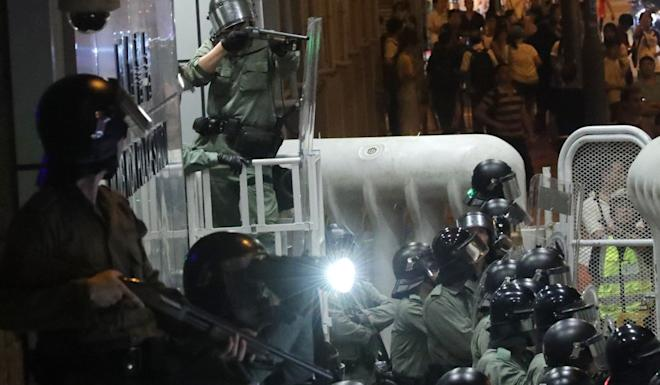 Riot police monitor the movement of protesters in front of Mong Kok Police Station on Friday. Photo: Edmond So