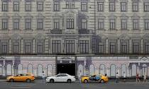 People walk past a building decorated with a giant banner in Moscow, Russia July 1, 2018. REUTERS/Gleb Garanich