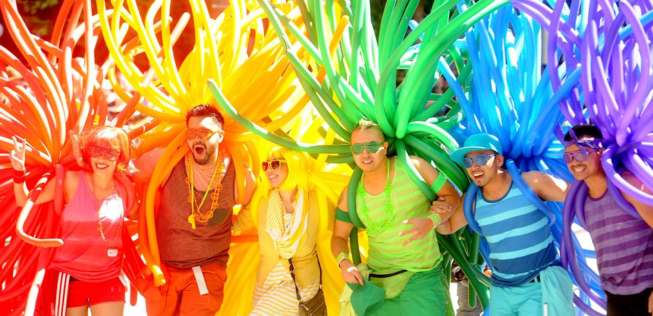 Revelers with balloons create a human rainbow during San Francisco's 42nd annual Gay Pride Parade on Sunday, June 24, 2012. The sidewalks of downtown San Francisco were crowded with colorful revelers on Sunday as the city marked its 42nd year celebrating the lesbian, gay and transgender community. (AP Photo/Noah Berger)