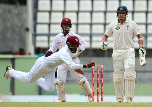 West Indies player Kraigg Brathwaite makes a flying catch to dismiss Australian batsman Ben Hilfenhaus (R) as Carlton Baugh looks on during the fourth day of the third test match between the West Indies and Australia in Roseau, Dominica