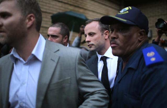 PRETORIA, SOUTH AFRICA - MARCH 03: Oscar Pistorius (2nd right) leaves North Gauteng High Court at the end of the first day of his trial accused of the murder of his girlfriend Reeva Steenkamp on March 3, 2014 in Pretoria, South Africa. Olympic and Paralympic athlete Oscar Pistorius, aged 27, is accused of murdering his girlfriend Reeva Steenkamp. Pistorius denies the allegation claiming he mistook Steenkamp for an intruder inside their home on Valentines Day 2013. (Photo by Christopher Furlong/Getty Images)
