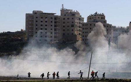 Palestinian protesters run away from tear gas fired by Israeli troops during clashes near Ramallah