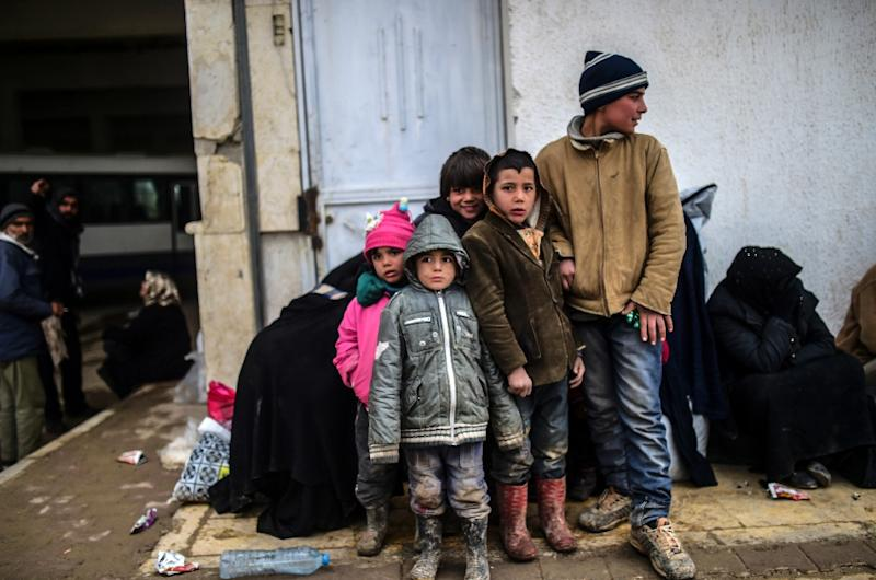 Refugee children wait near the Turkish border crossing gate as Syrians fleeing the northern embattled city of Aleppo wait on February 6, 2016 in Bab al-Salama, northern Syria (AFP Photo/Bulent Kilic)