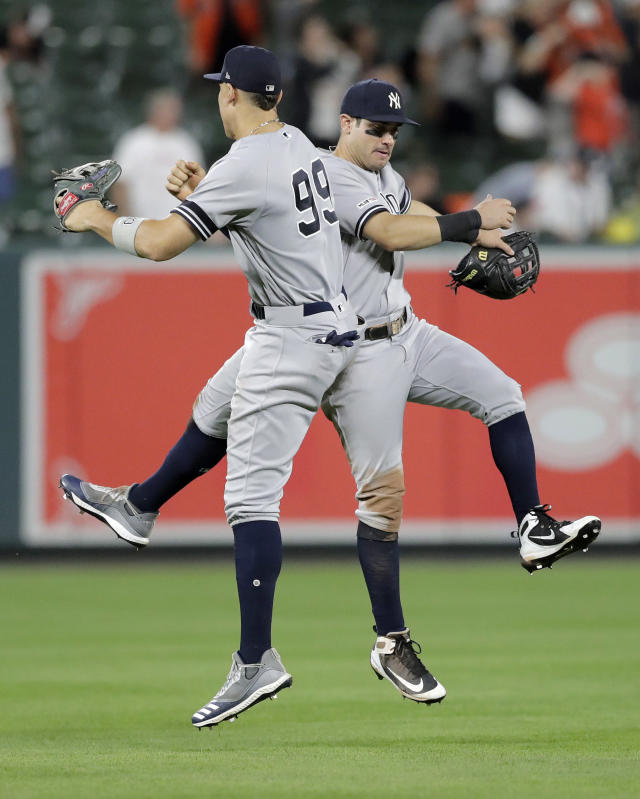 New York Yankees right fielder Aaron Judge (99) leaps with left fielder Mike Tauchman while celebrating the team's 9-4 win over the Baltimore Orioles in a baseball game Tuesday, Aug. 6, 2019, in Baltimore. (AP Photo/Julio Cortez)