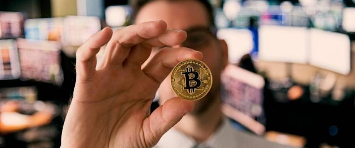 Man stands in office holding up bitcoin between thumb and forefinger to the camera.