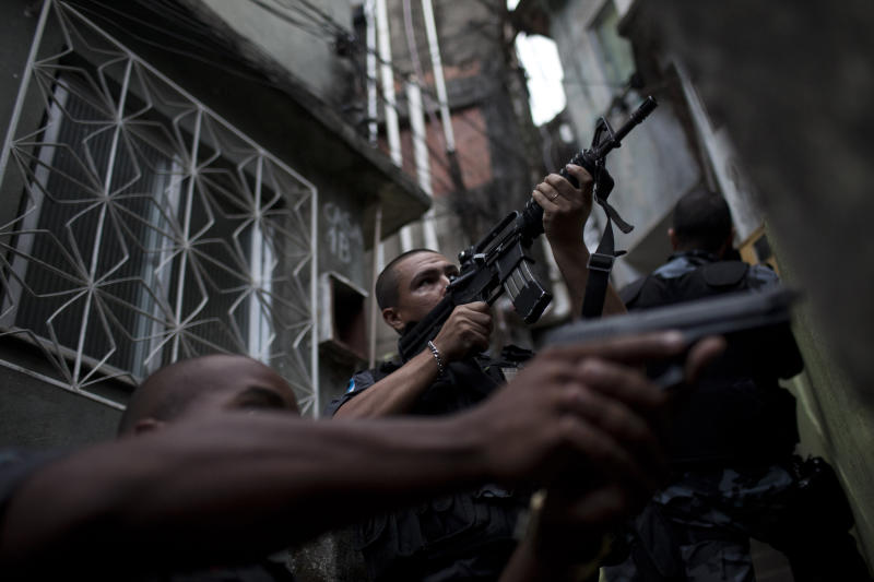 In this photo taken April 6, 2012, police patrol Rocinha slum in Rio de Janeiro, Brazil. Setbacks in a security program meant to take back territory from the drug trade have shown the immense challenge of pacifying the city's violent slums and raised questions about the state's ability to keep the peace as Rio prepares to take the world stage not just for the Olympics but the 2014 World Cup, which will host its headline events in Rio. (AP Photo/Felipe Dana)
