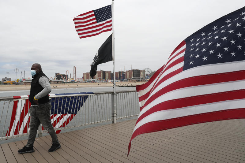 """Jonathan Eadie walks past three American flags he installed on the pier at Coney Island during the current coronavirus outbreak, on Memorial Day weekend, Sunday, May 24, 2020, in New York. Eadie says he has been putting up the flags whenever he can after he was furloughed from his job on March 23. He said, """"It makes me feel good to do this. Some people like it, and some don't."""" (AP Photo/Kathy Willens)"""