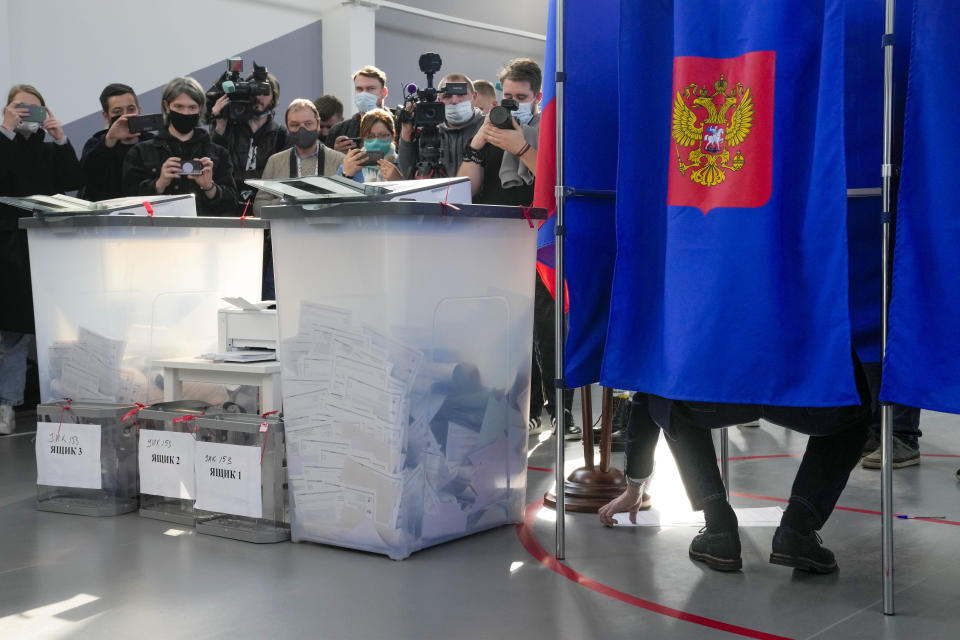Journalists wait to film St. Petersburg governor Alexander Beglov as he fills his ballot in a voting booth, right, during the State Duma, the Lower House of the Russian Parliament and local parliament elections at a polling station in St. Petersburg, Russia, Sunday, Sept. 19, 2021. The head of Russia's Communist Party, the country's second-largest political party, is alleging widespread violations in the election for a new national parliament in which his party is widely expected to gain seats. (AP Photo/Dmitri Lovetsky)
