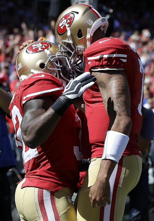 San Francisco 49ers running back Kendall Hunter, left, celebrates with quarterback Colin Kaepernick after running for a 13-yard touchdown against the Indianapolis Colts during the first quarter of an NFL football game in San Francisco, Sunday, Sept. 22, 2013. (AP Photo/Marcio Jose Sanchez)