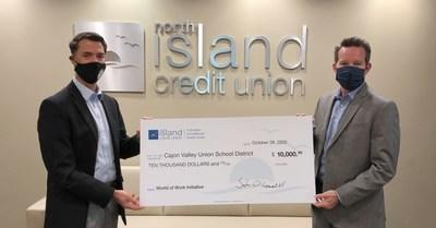 """Edward Hidalgo (left), Chief Innovation and Engagement Officer for the Cajon Valley Union School District (CVUSD), receives a $10,000 check on behalf of the District from Steve O'Connell, President/CEO of North Island Credit Union. As the Premier Sponsor of the Classroom of the Future Foundation (CFF), North Island Credit Union today presented the organization's prestigious Innovation in Education Impact Award to CVUSD for its """"World of Work"""" initiative. In recognition of the award, North Island Credit Union provided CVUSD with $10,000 to help ensure its career development program continues to empower teachers, students, and families throughout their K-12 educational experience."""