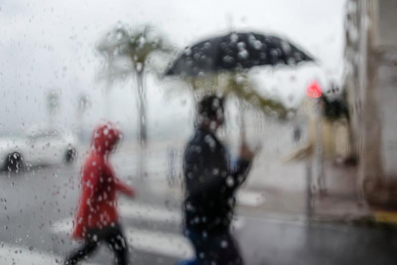 A person holding an umbrella and another walk behind a wet window in the French Riviera city of Nice, southern France on April 19, 2020. (Photo by VALERY HACHE / AFP) (Photo by VALERY HACHE/AFP via Getty Images)