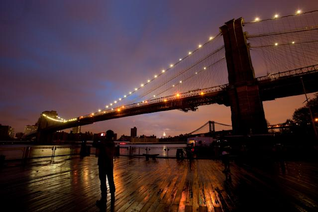 People stop along the Brooklyn waterfront to photograph the Brooklyn Bridge and the Manhattan skyline, Tuesday, Oct. 30, 2012 in New York. Much of lower Manhattan is without electric power following the impact of superstorm Sandy. (AP Photo/Mark Lennihan)