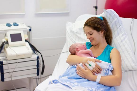 Mom holding newborn in a hospital bed