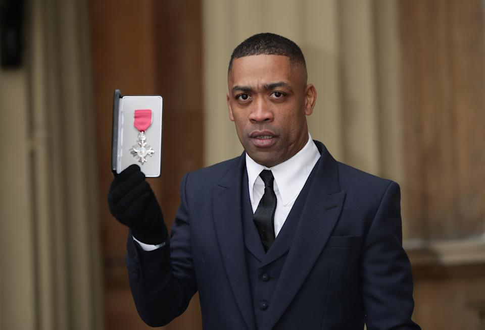 Musician Wiley, also known as Richard Cowie Jnr, holds his MBE following an investiture ceremony at Buckingham Palace, London.