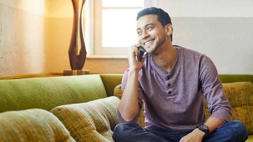 Smiling young man answering smart phone on couch.