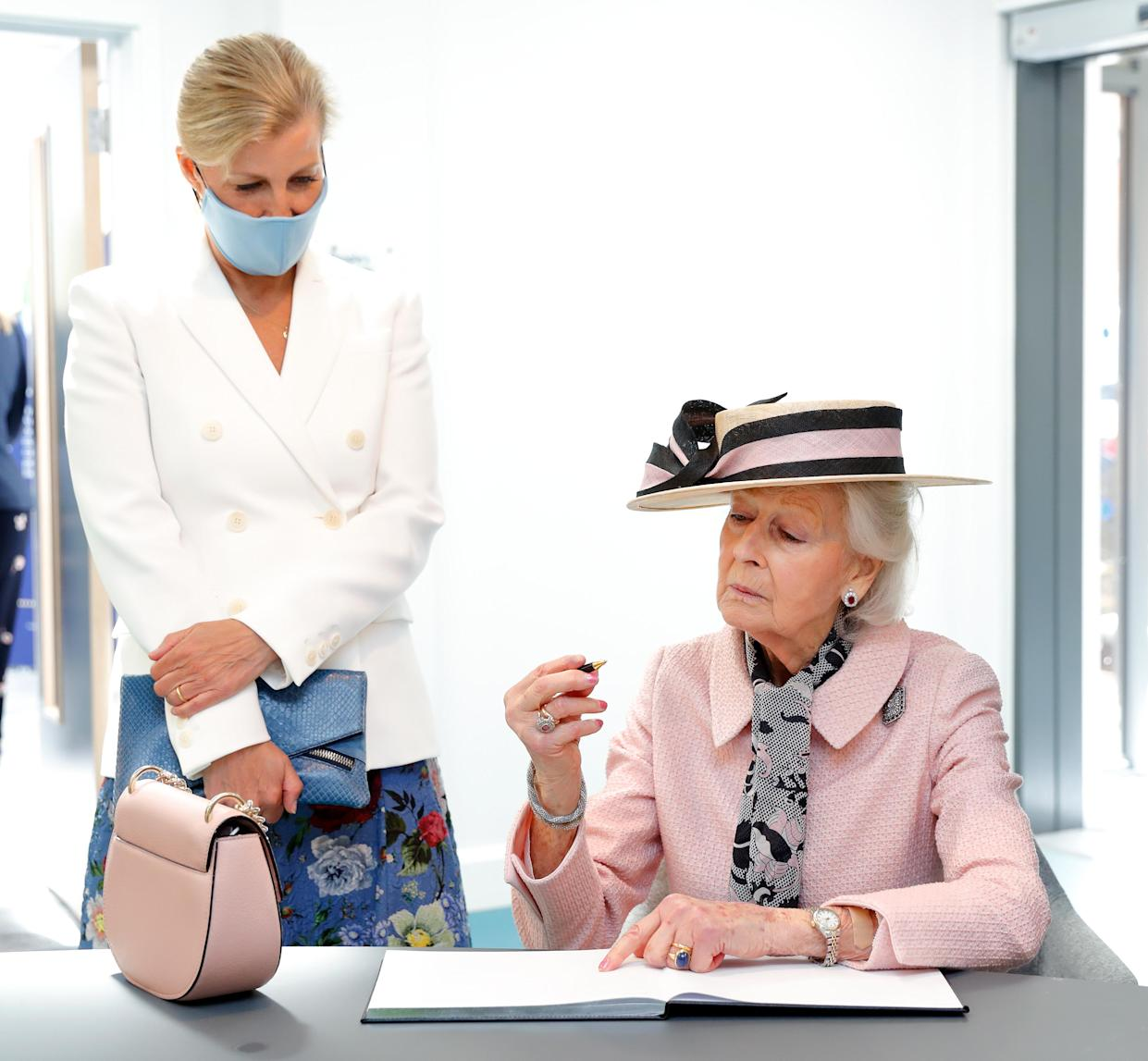 BRISTOL, UNITED KINGDOM - JULY 07: (EMBARGOED FOR PUBLICATION IN UK NEWSPAPERS UNTIL 24 HOURS AFTER CREATE DATE AND TIME) Sophie, Countess of Wessex looks on as Princess Alexandra signs the visitor's book during a visit to the Guide Dogs for the Blind Association to open their new south west regional centre and celebrate the charity's 90th anniversary on July 7, 2021 in Bristol, England. During the visit Princess Alexandra, who has been patron the Guide Dogs for the Blind Association since 1954, formally handed over the patronage to Sophie, Countess of Wessex. (Photo by Max Mumby/Indigo/Getty Images)